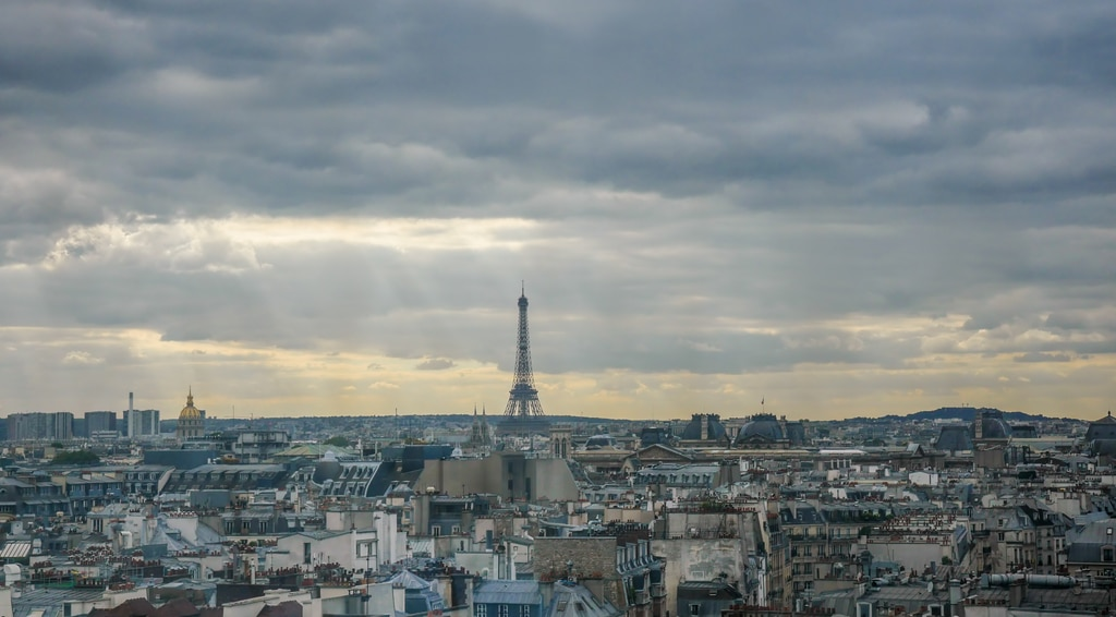 Small Eiffel Tower at horizon in France with sprawling urban landscape in foreground