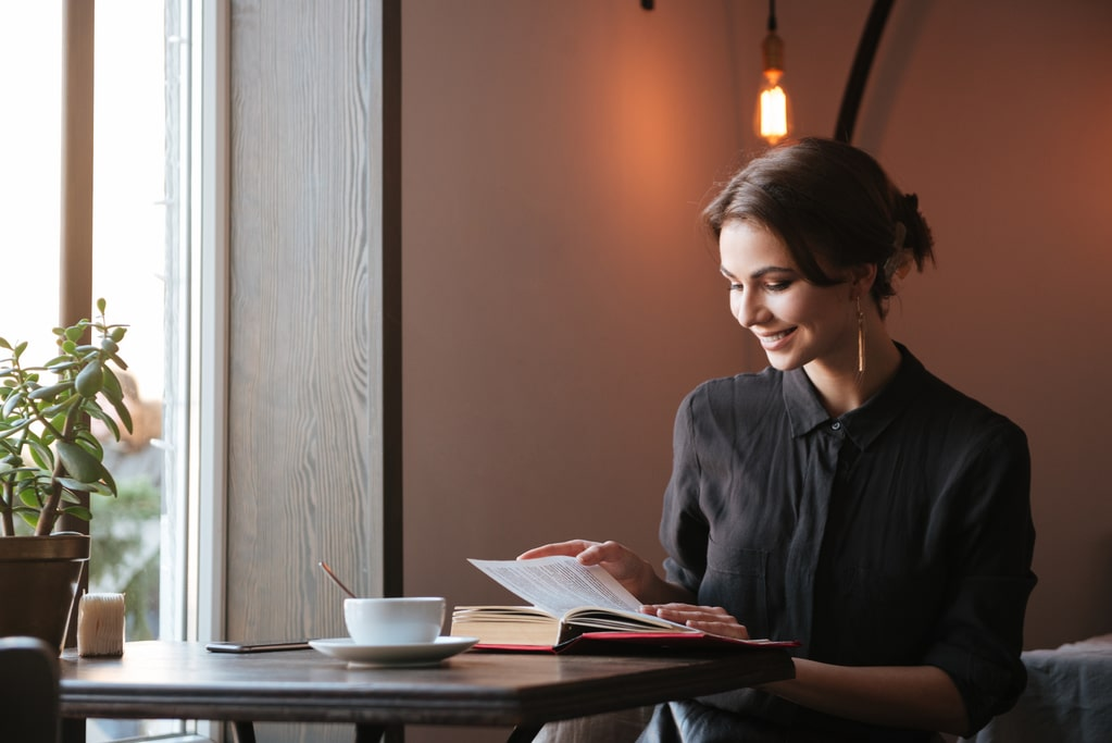 Photo of smiling young woman sitting at the table reading book in cafe and looking aside while drinking coffee.