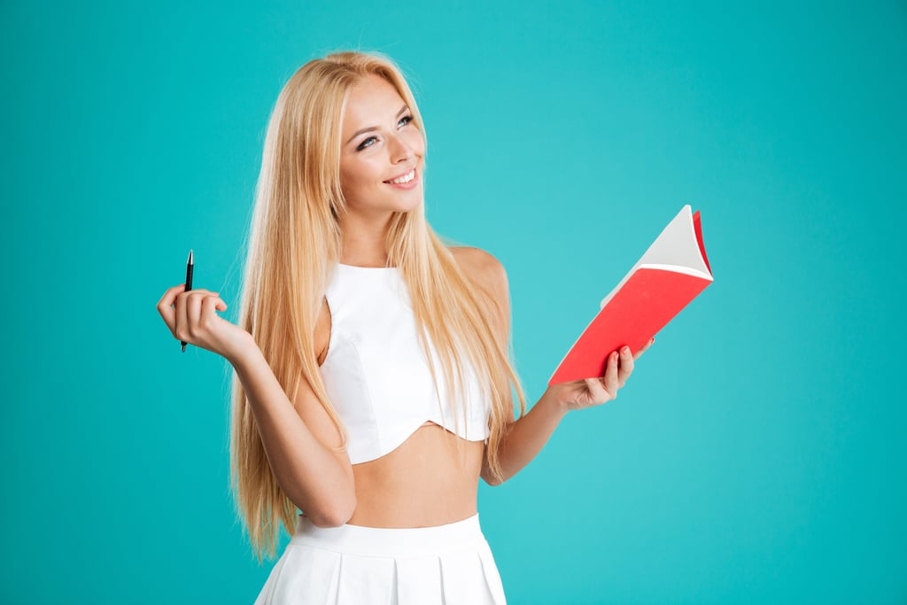 Portrait of a happy smiling girl holding notebook and pen and looking away isolated on the blue background