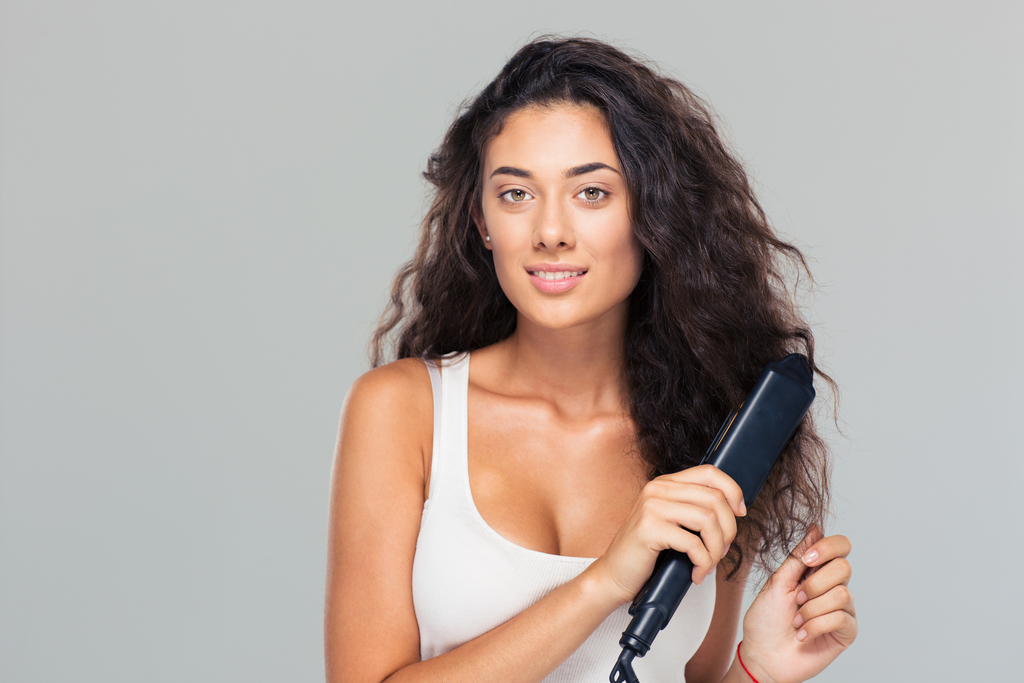Happy young Greek girl doing hairstyle with hair straightener over gray background