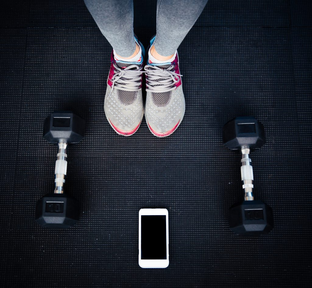 Closeup image of a female legs with dumbbells and smartphone on the floor at gym