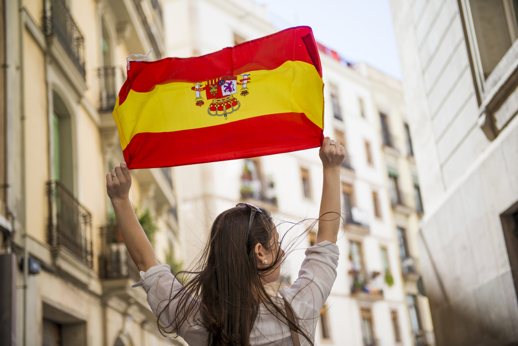 Happy Spanish girl tourist is walking in the city street of Barcelon with spanish flag.