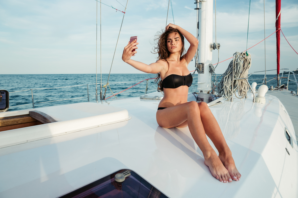 Young beautiful brunette Greek girl making selfie using phone while sitting on the luxury yacht