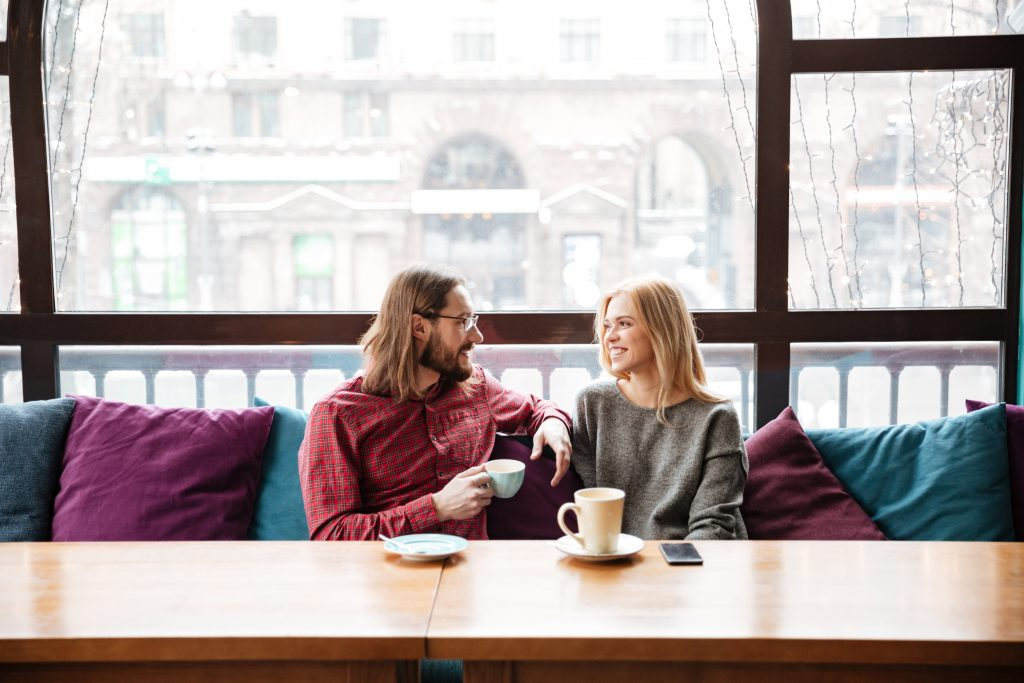 Image of young Polish laughing woman and bearded man friends sitting in cafe and talking while drinking coffee.