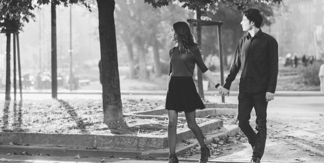 Young beautiful couple in love walking hand in hand in Kiev - first date, romantic, love concept - black and white filter